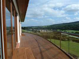 Large curved balcony in Royal Chrome handrail with a beautiful countryside view