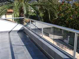 Balcony in the sun with silver handrail and palm trees in the garden