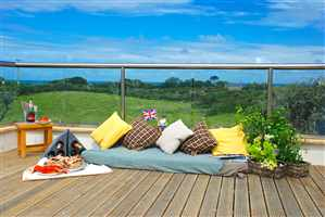 Countryside view from a straight Royal Chrome handrail balcony with cushions, plants and food