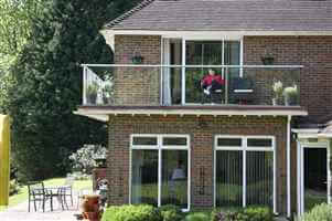 Woman enjoying her balcony with Royal Chrome handrails