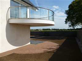 Curved balcony with Royal Chrome handrails overlooking the garden