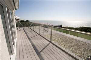 side view bronze handrail balustrading geese and the beach in view with blue sky