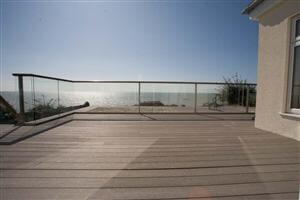 Large balcony with bronze handrail looking out at the stunning coast