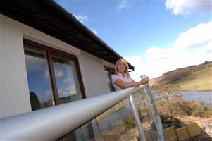 Side view of woman standing on her balcony leaning on the silver handrail