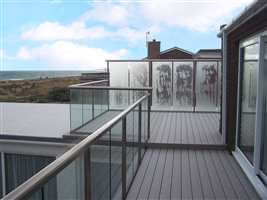 Royal Chrome handrail and posts with clear glass and privacy screens on the coast