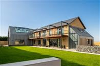 Striking glass balustrades supplied by Balconette add extra external space while opening up extensive countryside views at this unique self-built home.