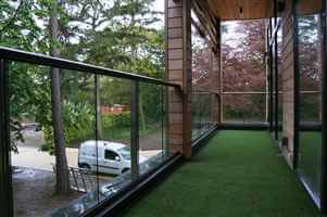 Royal Chrome aerofoil balconywith clear glass surrounded by woodland