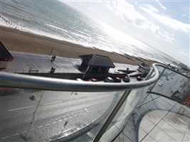 Curved balcony with Royal Chrome handrails and posts overlooking the sea