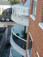 Curved balconies with silver handrails and privacy screens