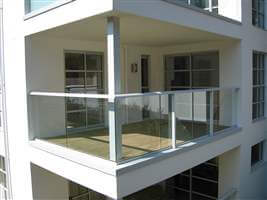 Spacious balcony with white handrails and posts on the corner of the building