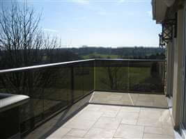 Bronze handrail balustrade with grey tinted glass overlooking beautiful countryside