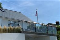 A bungalow framed with a beautiful glass balustrade makes an impressive panoramic view of the Kent coastline. Protecting the new terrace with wing-shaped handrail in a Royal Chrome finish.