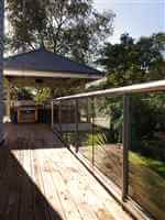 Long silver balustrading to a covered BBQ area surrounded by beautiful gardens
