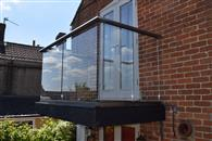 Replacing a rotten timber balcony with a clear glass one supplied by Balconette has given this semi-detached cottage in North Bradley, Wiltshire a contemporary new look to the delight of its owners Alan and Trudy Shellard.