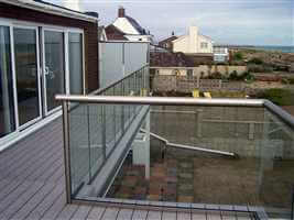 Royal Chrome balustrade with frosted glass privacy screens by the coast