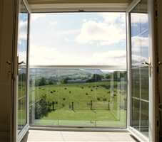 View to the beautiful country side through a Juliet balcony with a white handrail