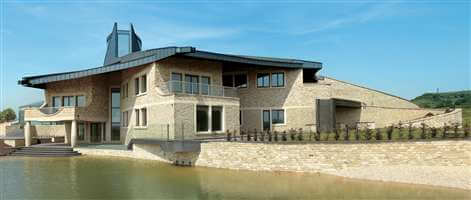 Large beautiful house with Silver balustrades surrounded by a lake