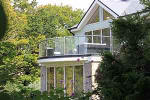 Looking through foliage at beautiful house with Royal Chrome balustrade