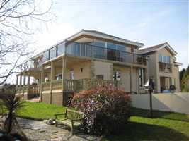Large house with Bronze handrail balcony with grey tinted glass, surrounded by beautiful views