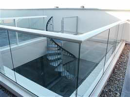 Barrier balustrade with silver aerofoil handrails and spiral staircase