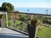 Lower maintencance and clear sea views are achieved by replacing an old wrought iron balcony with a glass and aluminium one from Balcony Systems.