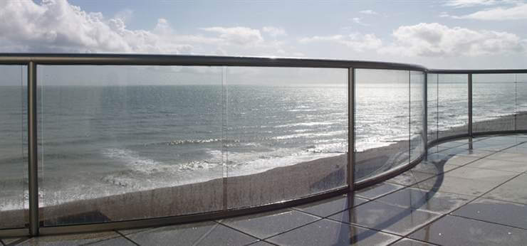 Glass Balustrade curved with Royal Chrome handrail by the sea