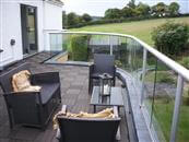 A large kitchen extension topped with a generous roof terrace and curved glass balcony balustrade has opened up spectacular views at their home near Bristol.