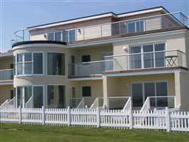 Curved and straight balustrades and Juliet balcony on coastal residency by the coast