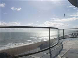 glass balustrade with chrome handrails on the seaside