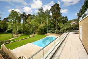 Long Royal Chrome balustrades over looking the blue swimming pool and garden