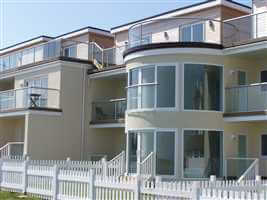 Silver Juliet balconies and balustrades on seafront residences surrounded by white picket fence