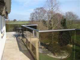 Wide zigzag balcony with bronze handrail and tinted glass looking over pretty views