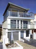 Interestingly designed clear glass balconies with silver handrails and posts