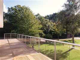 Wide balustrade with silver handrails and posts looking out to beautiful gardens