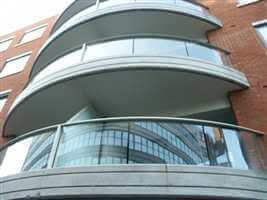 Curved balconies with silver handrails and posts on brick building
