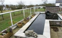 A 33-metre glass balustrade topped with a white powder-coated handrail turned into a perfect solution for a windy garden in Isle of Man property.