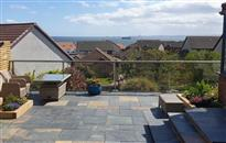 Glass balustrade has enhanced sea views from the sloping garden terrace in Kirkcaldy, Fife, Scotland. Glass panels on smart new patio provide wind protection.