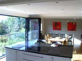 First floor kitchen with folding glass doors and wide Juliet balcony with Royal Chrome handrail