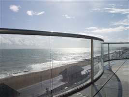 Curved balcony with a Royal Chrome handrails and posts with a view of the beach and blue skies
