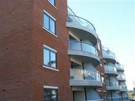 Side view of several curved balconies with silver handrail