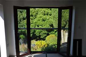 View to a sunny garden from a Royal Chrome Juliet balcony