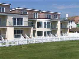 Silver Juliet balconies and balustrading surrounded by  white picket fence on the seafront