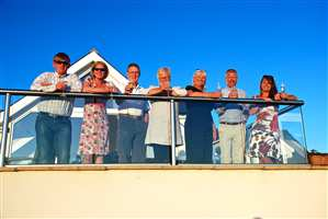 Family gathering on the balcony with clear glass and Royal Chrome handrails with the sun setting