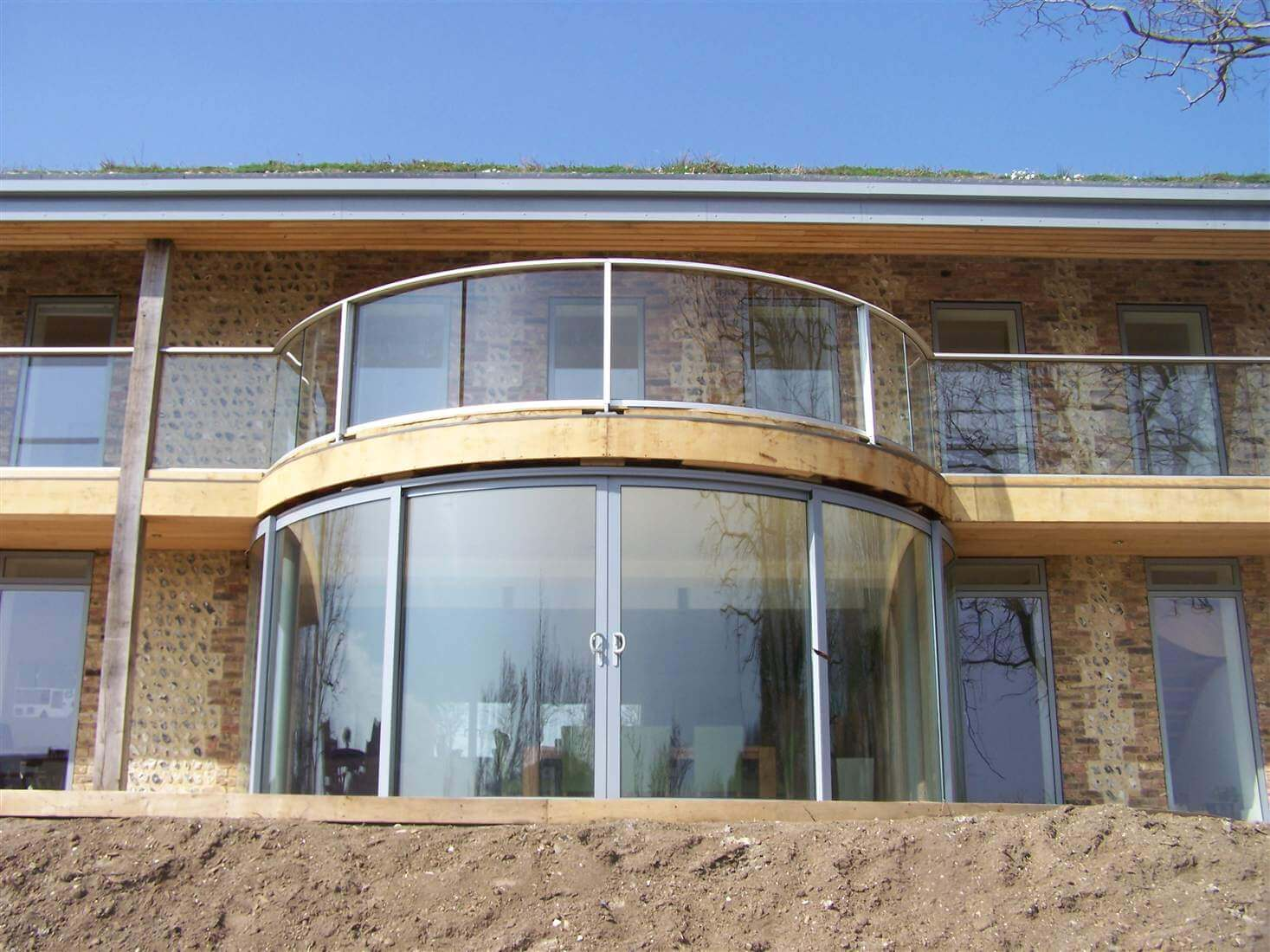 Curved Silver Aerofoil Balustrade With Curved Sliding Doors And Blue Sky