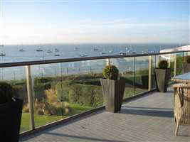 Bronze aerofoil handrail with clear glass balcony looking over the sea covered in yatchs and boats