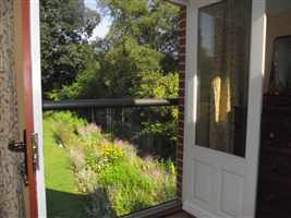 Looking out through a Bronze handrail Juliet balcony to a pretty garden