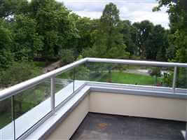 Corner countryside view through short clear glass balustrade with silver handrails and posts