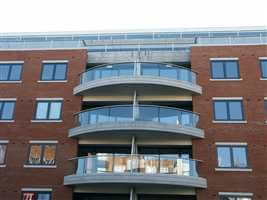 Curved silver balconies with privacy screens on brick building