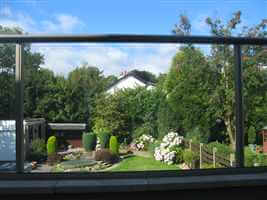 View of a colourful garden through clear glass balcony with Royal Chrome handrails