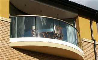 Curved semi frameless balcony with a Bronze handrail